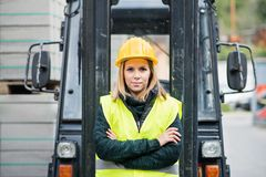Woman forklift truck driver in an industrial area. A woman standing in front of the fork lift truck outside a warehouse Royalty Free Stock Image