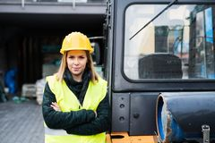 Woman forklift truck driver in an industrial area. A woman standing in front of the fork lift truck outside a warehouse Royalty Free Stock Photo