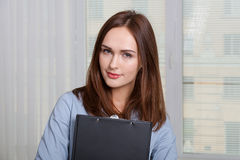 Woman in formal attire holding a folder Royalty Free Stock Images