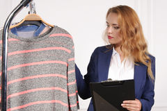 Woman in formal clothes chooses shirt in a clothing store royalty free stock image