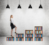 A woman in formal clothes is going up on the bookshelf. A concept of different level of education. Concrete room with four black c Stock Photo
