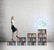 A woman in formal clothes is going up on the bookshelf. A concept of different level of education. Sketched brain on the final ste Royalty Free Stock Photography