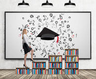 A woman in formal clothes is going up on the bookshelf. A concept of different level of education. A sketched graduation hat and d. Ifferent educational icons on royalty free stock images