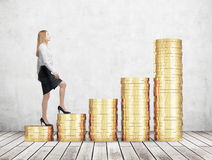 A woman in formal clothes is going up using a stairs which are made of golden coins. A concept of success. Royalty Free Stock Images