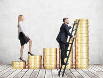 A woman in formal clothes is going up using a stairs which are made of golden coins, while a man has found a shortcut how to reach Stock Photography