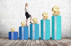 A woman in formal clothes is going up using a stairs which are made of houses. A concept of success. Dollar signs are on each buil Stock Photography