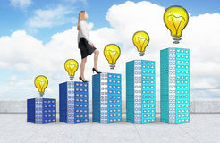 A woman in formal clothes is going up using a stairs which are made of houses with lightbulbs. A concept of new ideas and success. Stock Image
