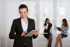 Woman in formal clothes reading information from the tablet smil Royalty Free Stock Photos