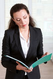 Woman in formal clothes reads information from a folder Stock Photography