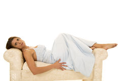 Woman in a formal laying on a couch looking stock photography