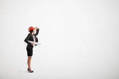 Woman in formal wear and construction helmet holding blueprints Royalty Free Stock Image