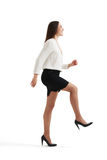 Woman in formal wear doing one step. Smiley businesswoman in formal wear doing one step and looking forward. isolated on white background Stock Images