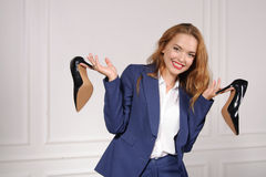 Woman in formal wear holding in each hand shoes Royalty Free Stock Image