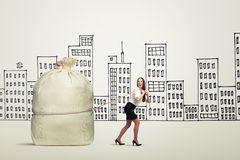Woman in formal wear pulling big bag. Funny woman in formal wear pulling big bag over drawing city stock photography