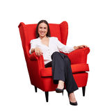 Woman in formal wear sitting on red chair Stock Photography