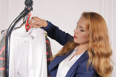Woman in formal wear takes his shirt off the rack Stock Photos