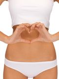 Woman forming heart shape on belly stock photo