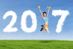 Woman forming numbers 2017 on the meadow Stock Photos