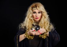 Woman fortune teller with crystal ball portrait. On black Royalty Free Stock Images