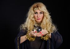 Woman fortune teller with crystal ball portrait. On black Stock Image
