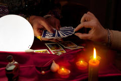 Woman fortune teller holding tarot cards in her hands. And another woman picking the card stock image