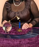 Woman fortune teller. Woman puts out the candle after divination on Tarot cards Stock Photography