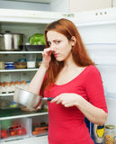 Woman with foul food near refrigerator. Long-haired woman in red holding nose because of bad smell near fridge at home royalty free stock image