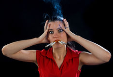 Woman with four cigarettes. In cloud of smoke Stock Photography