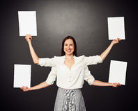 Woman with four hands holding white boards Stock Image