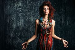 Woman with foxy hair. Beautiful bright woman with curly foxy hair wears a dress and beads in boho style. Ethnic style in clothes Royalty Free Stock Photos
