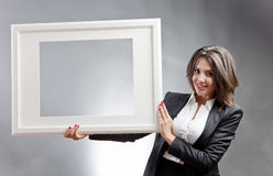Woman with frame. Young business woman holding a blank photo frame Royalty Free Stock Images