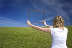 Woman with frame on big meadow. Young woman with frame and two harts one on grass next on sky stock image