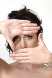 Woman frame eyes with hands. Woman framing eyes with hands stock photography