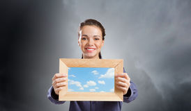 Woman with frame. Young woman in shirt with wooden frame in hands Stock Image