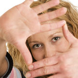 Woman framing eyes with hands Stock Photos