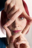 Woman framing face with fingers Stock Images