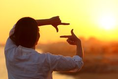 Woman framing with fingers at sunset Royalty Free Stock Photos