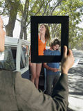Woman framing a young couple standing by van on a road trip Stock Images