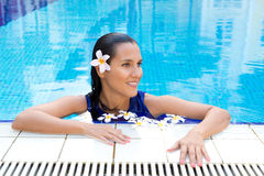 woman with frangipani flower in hair, relaxing in the pool in full blue dress Stock Images