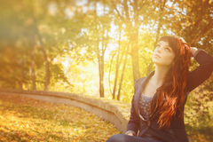 Woman with freckles and red long hair in fall park Royalty Free Stock Photography