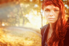 Woman with freckles and red long hair in fall park Stock Photo