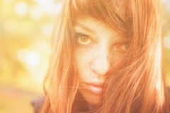 Woman with freckles and red long hair in fall park Royalty Free Stock Image