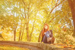 Woman with freckles and red long hair in fall park Royalty Free Stock Photos