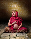 Woman in free clothes in the lotus position Stock Photo