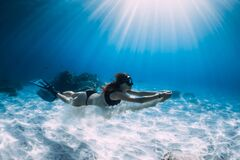 Free Woman Free Diver Glides With White Sand Over Sandy Sea. Freediving Underwater In Hawaii Royalty Free Stock Photography - 176039367