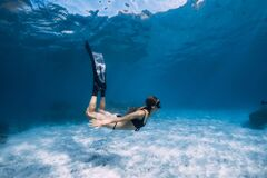 Free Woman Free Diver Glides With White Sand Over Sandy Sea. Freediving Underwater In Hawaii Stock Photos - 176613993