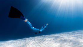 Woman freediver glides over sandy bottom Royalty Free Stock Photos