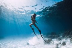 Woman freediver glides over sandy sea with fins. royalty free stock photo