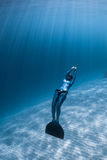 Woman freediver relaxes. Underwater with monofin over sandy bottom Stock Photos