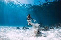Free Woman Freediver With White Sand Glides Over Sandy Sea With Fins. Freediving Underwater Stock Photos - 150382523
